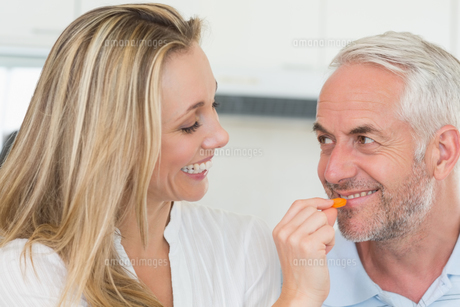 Happy woman feeding her partner vegetable pieceの写真素材 [FYI00001536]