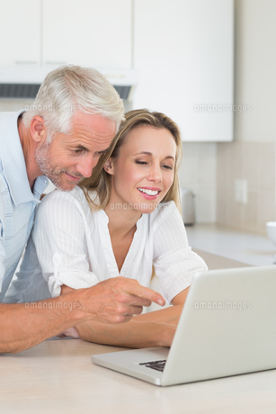 Happy couple using laptop together at the counterの写真素材 [FYI00001537]