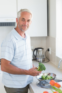 Casual man rinsing broccoli in colander and smiling at cameraの素材 [FYI00001543]