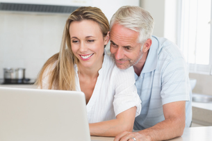 Happy couple using laptop together at the counterの写真素材 [FYI00001545]