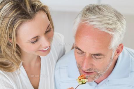 Happy woman feeding her partner a spoon of vegetablesの写真素材 [FYI00001546]