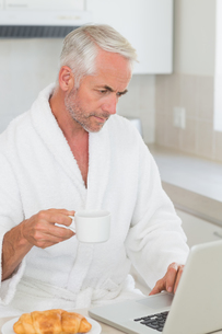 Serious man using laptop at breakfast in a bathrobeの写真素材 [FYI00001550]
