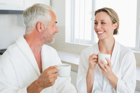 Smiling couple having coffee at breakfast in bathrobesの写真素材 [FYI00001551]