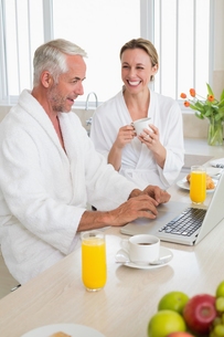 Smiling couple using laptop at breakfast in bathrobesの写真素材 [FYI00001552]