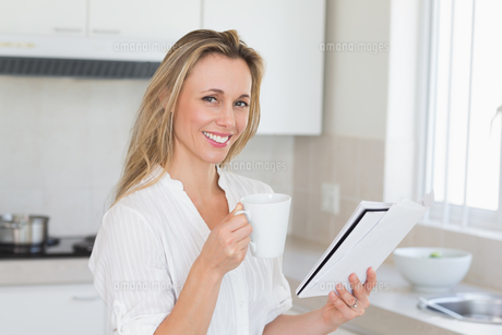 Smiling woman holding mug and newspaperの写真素材 [FYI00001553]
