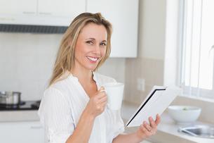 Smiling woman holding mug and newspaperの写真素材 [FYI00001553]