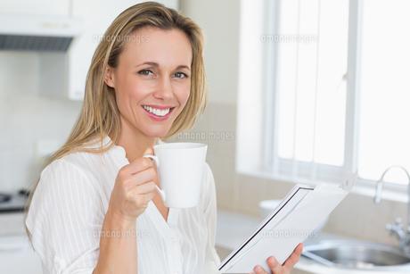 Smiling woman holding mug and newspaperの写真素材 [FYI00001554]