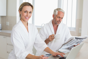 Couple shopping online and reading newspaper in bathrobesの写真素材 [FYI00001555]