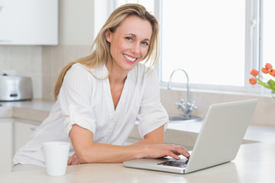 Happy woman using laptop at counterの写真素材 [FYI00001557]