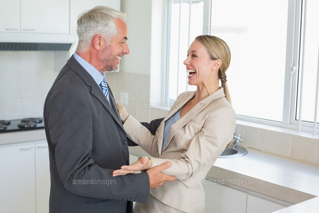 Happy business couple laughing together before work in morningの写真素材 [FYI00001558]