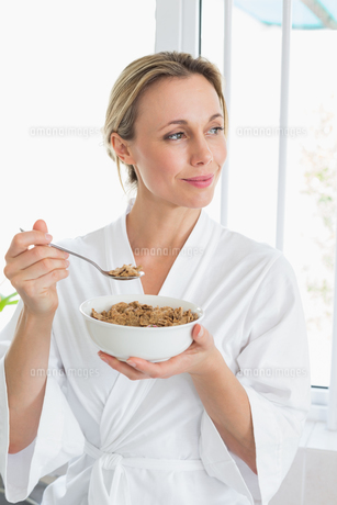 Smiling woman in bathrobe having cerealの写真素材 [FYI00001559]