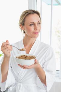 Smiling woman in bathrobe having cerealの写真素材 [FYI00001559]