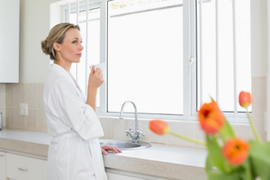 Thoughtful woman in bathrobe standing with coffee cupの写真素材 [FYI00001561]