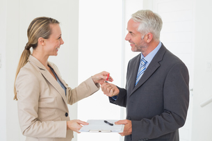 Smiling estate agent giving house key to happy customerの写真素材 [FYI00001568]