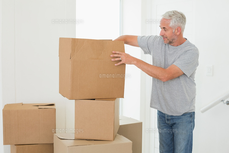 Smiling man looking at cardboard moving boxesの写真素材 [FYI00001570]
