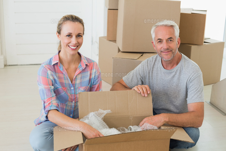Happy couple unpacking cardboard moving boxesの写真素材 [FYI00001571]