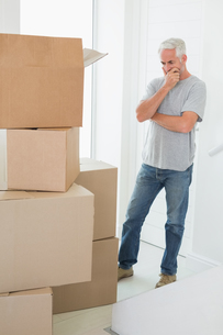 Thoughtful man looking at cardboard moving boxesの写真素材 [FYI00001572]
