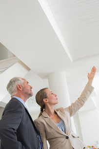 Smiling estate agent showing ceiling to potential buyerの写真素材 [FYI00001574]