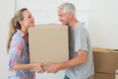 Happy couple carrying cardboard moving boxesの写真素材 [FYI00001575]