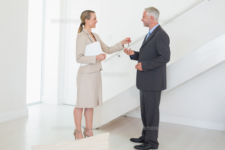Smiling estate agent handing over keys to customerの写真素材 [FYI00001576]