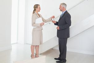 Smiling estate agent handing over keys to customerの写真素材 [FYI00001576]