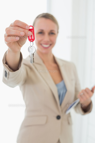 Smiling estate agent showing keys to cameraの写真素材 [FYI00001577]