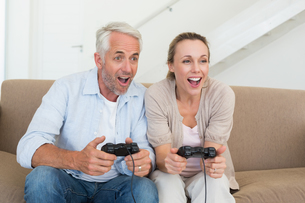 Happy couple having fun on the couch playing video gamesの写真素材 [FYI00001584]
