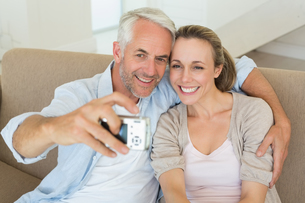 Happy couple taking a selfie together on the couchの写真素材 [FYI00001590]