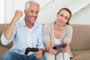 Happy couple having fun on the couch playing video gamesの写真素材 [FYI00001591]