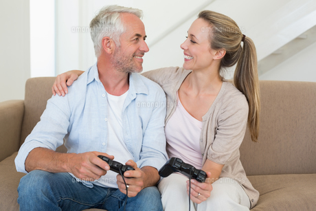 Happy couple having fun on the couch playing video gamesの写真素材 [FYI00001592]