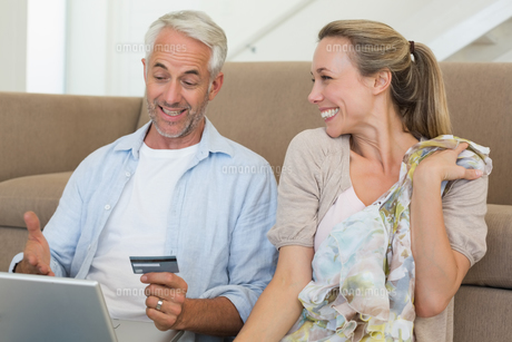 Happy couple shopping online on the couchの写真素材 [FYI00001595]