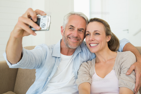 Happy couple taking a selfie together on the couchの写真素材 [FYI00001596]