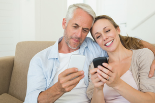 Happy couple sitting on couch texting on their phonesの写真素材 [FYI00001597]