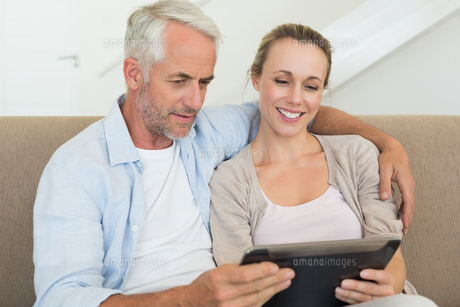 Happy couple using tablet pc together on the couchの写真素材 [FYI00001598]