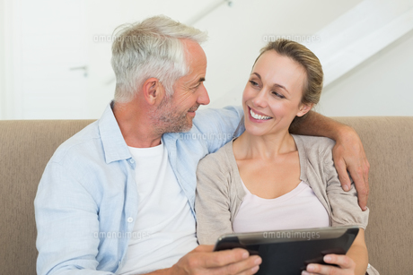 Happy couple using tablet pc together on the couchの写真素材 [FYI00001599]