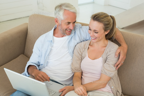 Happy couple using the laptop together on the couchの写真素材 [FYI00001601]