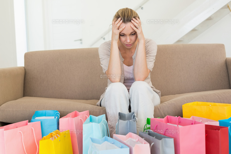 Regretful woman looking at many shopping bags on the couchの素材 [FYI00001602]