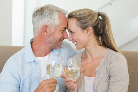Happy couple sitting on couch toasting with white wineの素材 [FYI00001605]