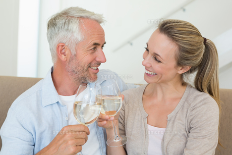 Happy couple sitting on couch toasting with white wineの素材 [FYI00001606]