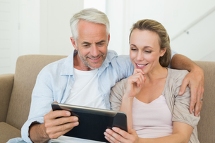 Happy couple using tablet pc together on the couchの写真素材 [FYI00001607]