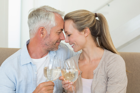 Happy couple sitting on couch toasting with white wineの写真素材 [FYI00001608]