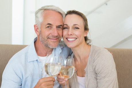 Happy couple sitting on couch toasting with white wineの素材 [FYI00001612]