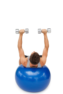Young man exercising with dumbbells on fitness ballの写真素材 [FYI00001613]