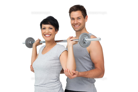 Personal trainer helping woman with weight lifting barの写真素材 [FYI00001615]