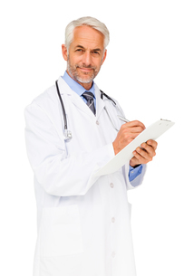 Portrait of a confident male doctor writing reportsの写真素材 [FYI00001632]