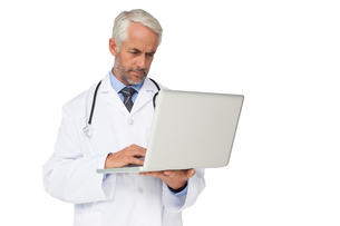Concentrated male doctor using laptopの写真素材 [FYI00001633]