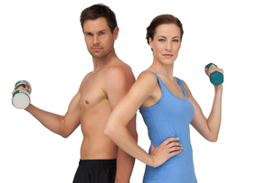 Fit young couple exercising with dumbbellsの写真素材 [FYI00001635]