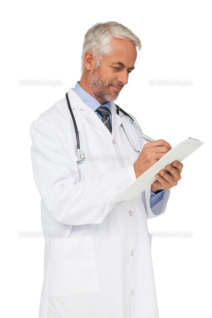 Concentrated male doctor writing reportsの写真素材 [FYI00001640]
