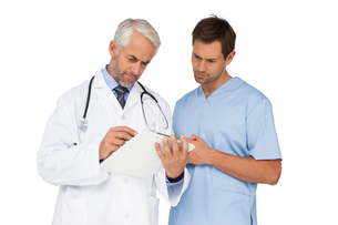 Male doctor and surgeon looking at reportsの写真素材 [FYI00001647]