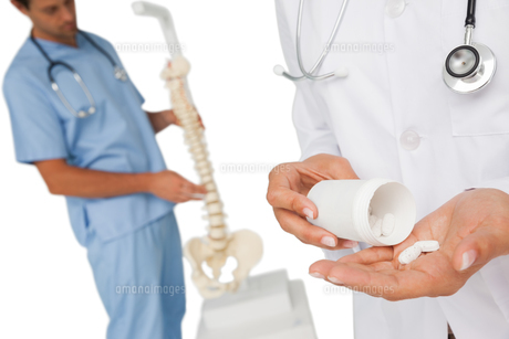 Mid section of female doctor with pills and skeleton modelの写真素材 [FYI00001657]